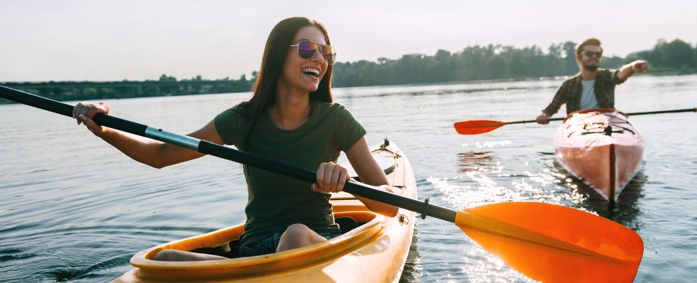 Couple kayaking man points at something not within frame while woman smiles