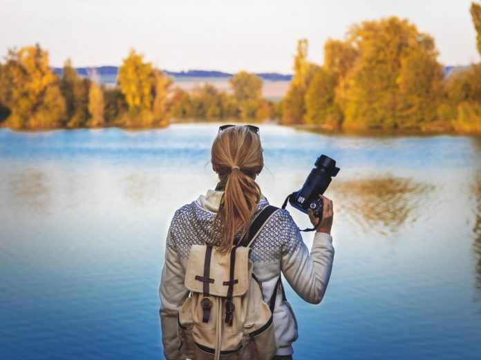 Person hiking with a camera. Taking photos of fall foliage around a lake.