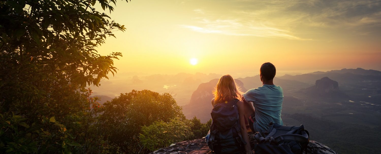 two people sitting on a mountain looking out over the views
