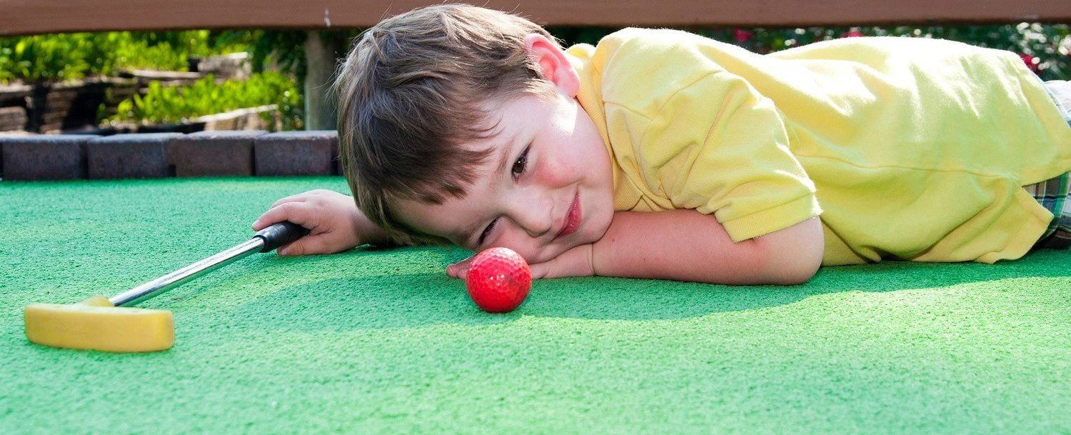 Young boy plays mini golf on putt putt course