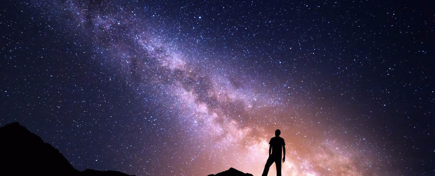 Landscape with Milky Way. Night sky with stars and silhouette of a happy man on the rock. Beautiful Universe. Space background