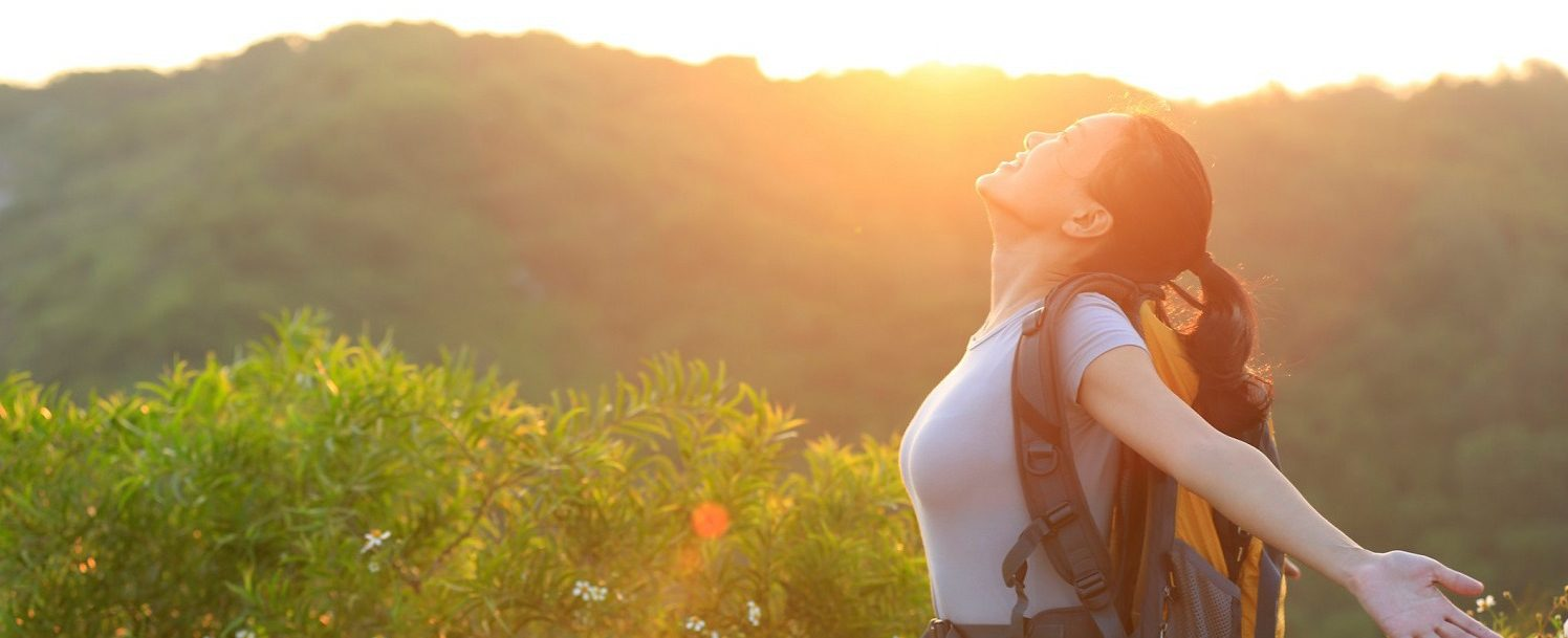 Woman hiking with a backpack on at sunset.