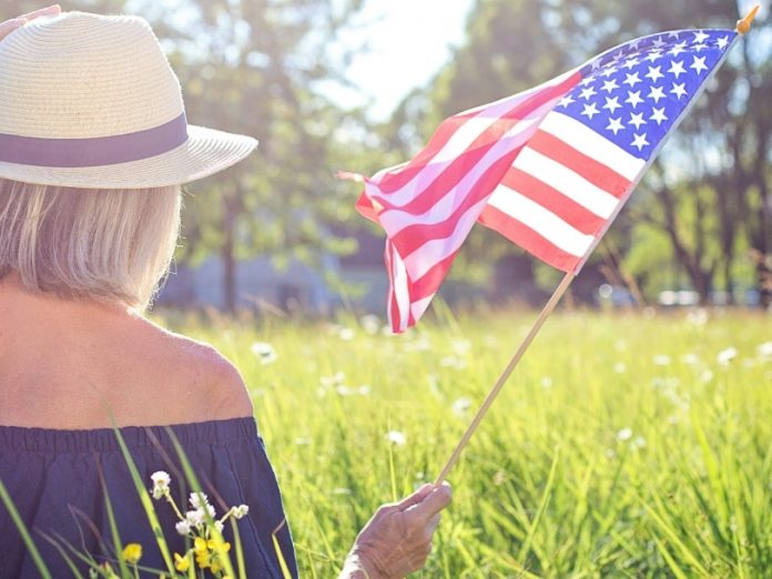 Woman with hat on sits in a green field holding USA flag