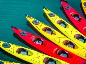 Red and yellow kayaks tied up together in the water